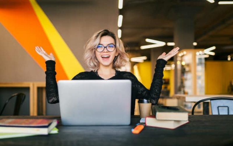 funny-happy-excited-young-pretty-woman-sitting-table-black-shirt-working-laptop-co-working-office-wearing-glasses_285396-86 (1)